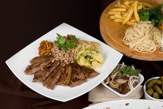 Molti piatti di cibo sul tavolo. piatto di carne da vicino.