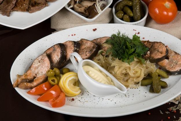 Molti piatti di cibo sul tavolo. piatto di pesce vicino.