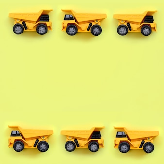 Molti piccoli camion gialli del giocattolo su struttura di giallo pastello di modo