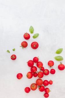 Molti pomodori rossi con foglie di basilico su sfondo con texture
