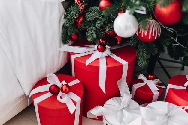 Molti regali di natale meravigliosamente avvolti in rosso e bianco sotto l'albero di natale