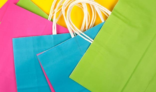 Molti shopper in carta multicolor con manici bianchi