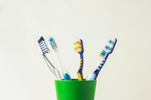 Molti spazzolini da denti in un bicchiere di plastica su uno sfondo bianco. il concetto di cambiare spazzolini da denti, igiene orale, odontoiatria, una famiglia numerosa e amichevole.
