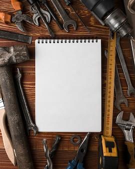 Molti strumenti utili e taccuino in bianco sulla tavola di legno, vista superiore