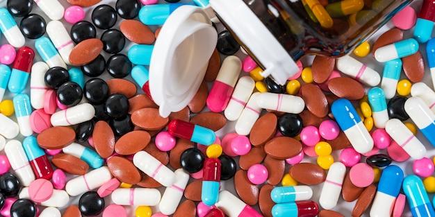 Molti tipi di capsule delle pillole delle droghe mediche su bianco