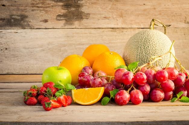 Molti tipi di frutta collocati su un pavimento di legno.