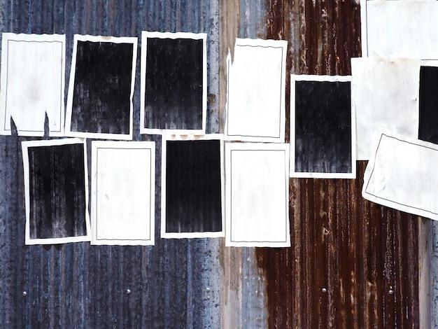 Molti vecchi manifesti pubblicitari in bianco sulla parete arrugginita dello zinco del metallo ondulato