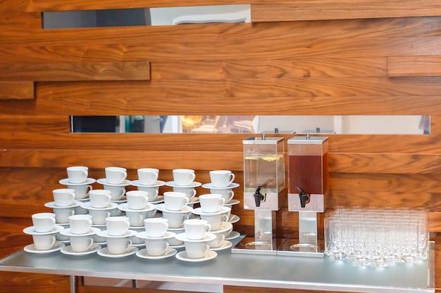 Molti vuoti tazze da tè o caffè bianco, bicchieri e grandi bottiglie di succo sul tavolo. servizio di catering per eventi.