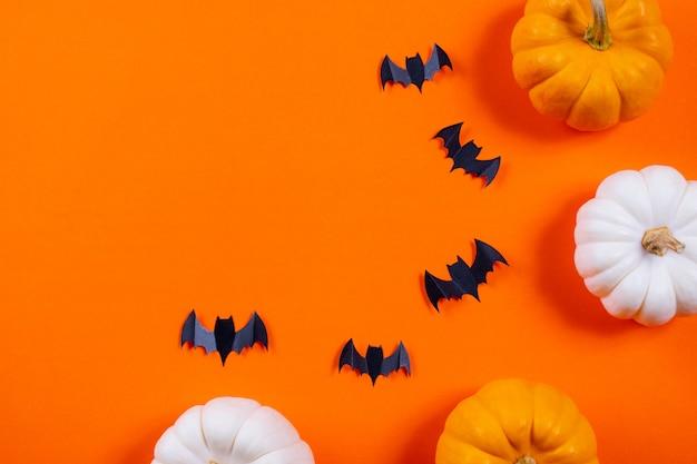 Moltitudine di pipistrelli di carta neri e zucca fresca su fondo di carta arancio.