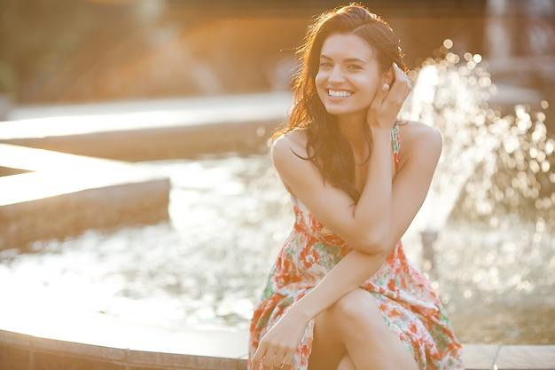 Molto bella donna seduta vicino alla fontana. signora in vestito rosso in ritratto del primo piano di estate. femmina attraente.