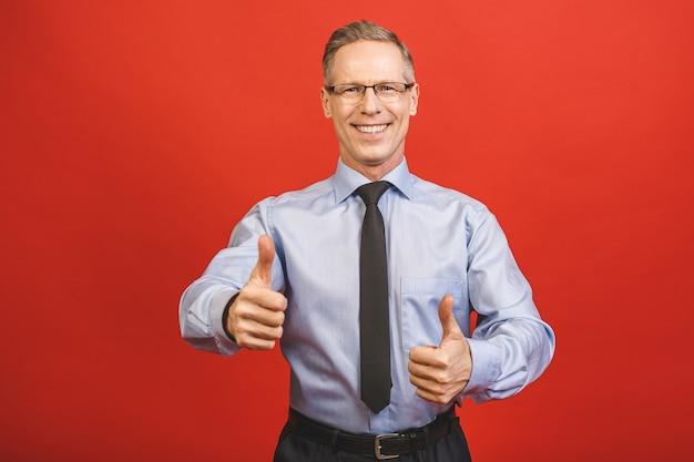 Molto bene! chiuda sul ritratto dell'uomo di affari senior invecchiato emozionante allegro allegro contento fresco sicuro sicuro delizioso che dimostra il pollice sul sorriso isolato sulla parete rossa.