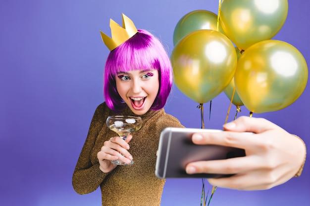 Momenti di celebrazione di felice anno nuovo di giovane donna eccitata con taglio di capelli rosa che fa il ritratto del selfie. abito di lusso, palloncini dorati, cocktail alcolico, festa di compleanno.