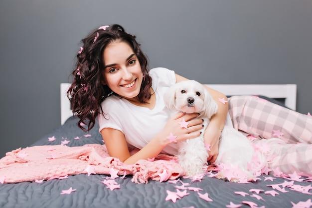 Momenti dolci felici di giovane bella donna in pigiama con capelli ricci castani tagliati agghiacciante sul letto con cagnolino in appartamento moderno. sorridere in orpelli rosa, rilassarsi nell'intimità di casa