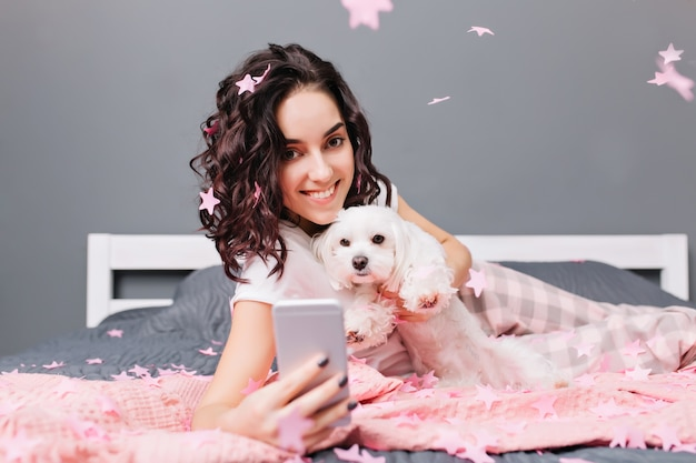 Momenti dolci felici di giovane bella donna in pigiama con capelli ricci castani tagliati facendo selfie foto con il cane in orpelli rosa sul letto in appartamento moderno. sorridere, esprimere positività