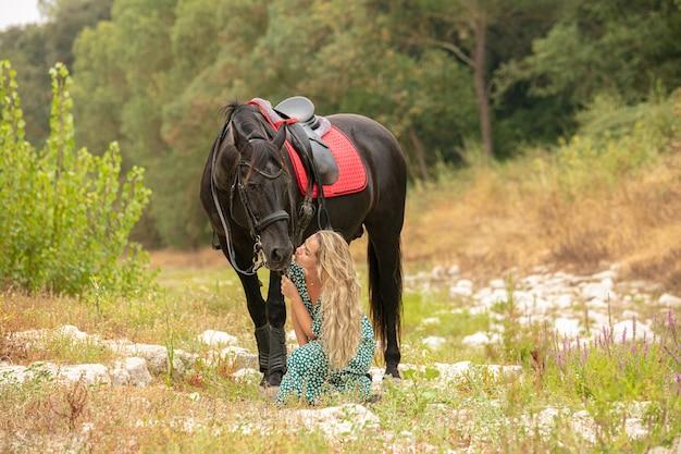 Momento di amicizia tra una donna vestita e un cavallo nero
