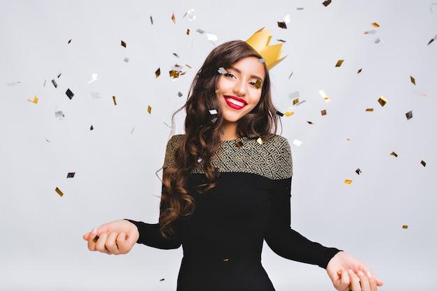 Momento felice, giovane donna sorridente che celebra il nuovo anno, vestito nero e corona gialla, festa in discoteca di carnevale felice, coriandoli scintillanti, divertirsi, sorridere.