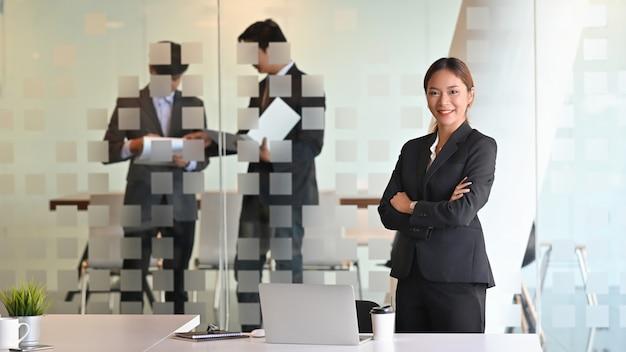 Momento fiducioso della donna di affari asiatica che sta sulla parte anteriore della sala riunioni.