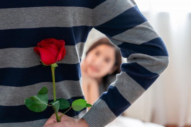 Momento inaspettato giorno di san valentino, giovane coppia innamorata e un uomo nascosto tenendo sorpresa rosa rossa dietro la schiena per la bella giovane donna