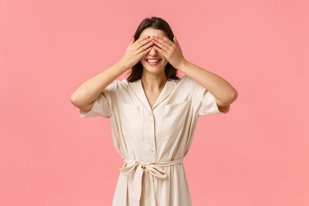 Momento romantico, concetto di bellezza e tenerezza. attraente ragazza bruna che chiede gli occhi da vicino, coprire la vista con le palme come regalo di sorpresa in attesa, in piedi muro rosa, sorridendo con la tentazione