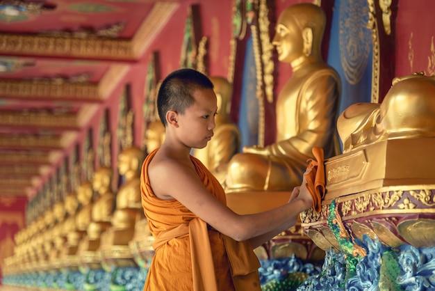 Monaci alle prime armi e statua del buddha, monk il giovane monaco buddista del sud-est asiatico in uno dei templi della thailandia.