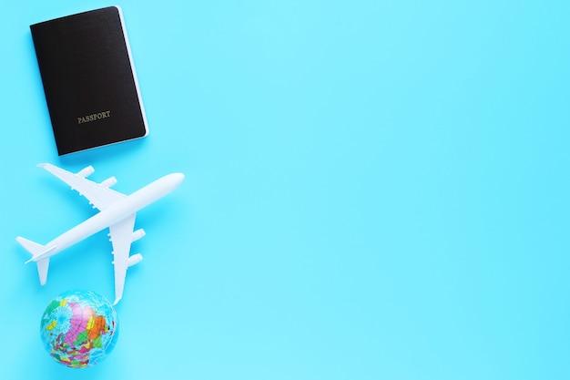 Mondo, modello di aereo e passaporto su sfondo blu. concetto di viaggio con copia spazio