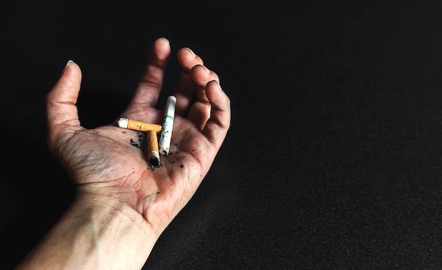 Mondo senza concetto di giorno del tabacco. sigarette nelle mani di uomini che stanno morendo di cancro