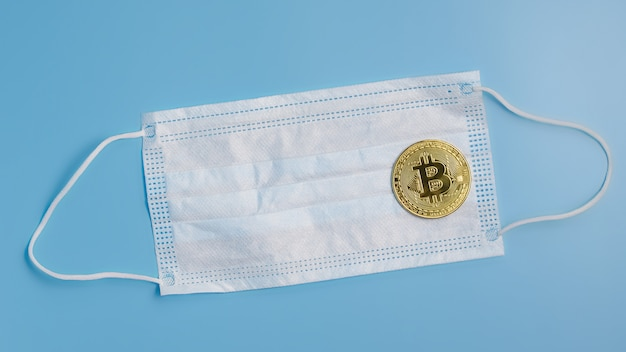 Moneta bitcoin e maschera chirurgica protettiva su sfondo blu. concetto di epidemia di virus. equipaggiamento protettivo dal coronavirus.