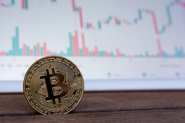Moneta d'oro bitcoin e grafico a candele