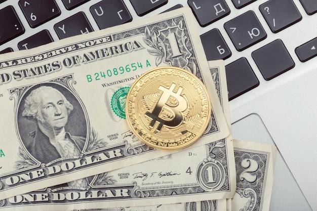 Moneta d'oro bitcoin e una banconota da un dollaro