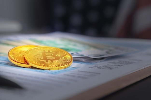 Moneta d'oro bitcoin su dollari americani da vicino. criptovaluta elettronica