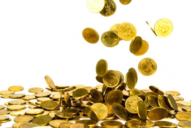 Moneta d'oro che cade isolato su bianco