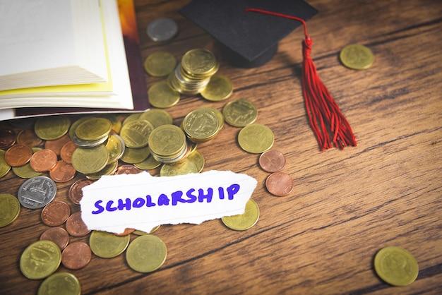 Moneta dei soldi su legno con sfondo scuro e cappello di laurea sul libro aperto
