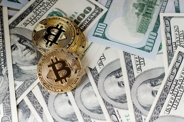 Moneta di bitcoin dell'oro fisica contro le fatture del dollaro e lo smartphone su una priorità bassa viola.