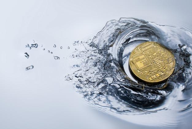 Moneta dorata del bitcoin con il concetto di valuta cripto della spruzzata dell'acqua.