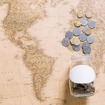 Monete che fuoriescono dal barattolo sulla mappa del mondo