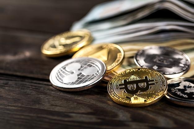 Monete d'argento e d'oro con simbolo bitcoin, ripple ed ethereum su legno.