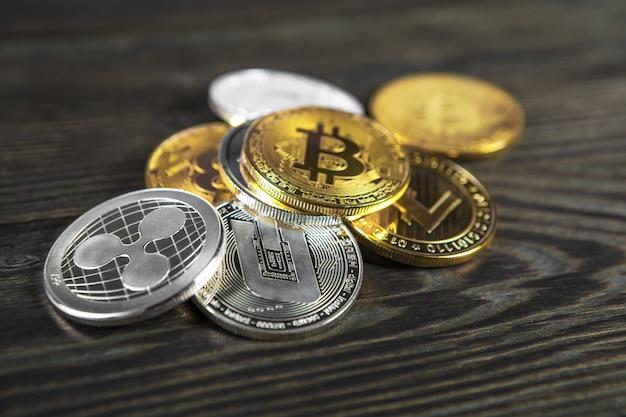 Monete d'argento e d'oro con simbolo bitcoin, ripple ed ethereum