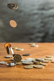 Monete d'argento e d'oro e monete che cadono sul tavolo di legno