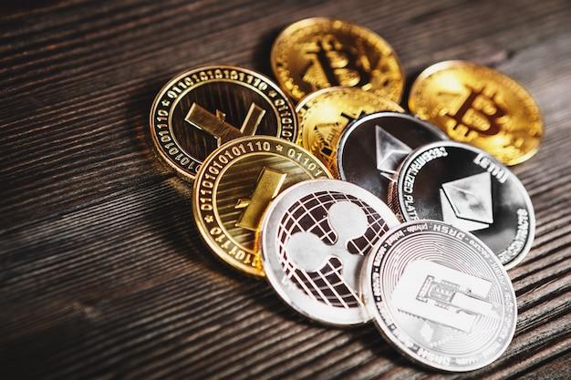 Monete d'argento e dorate con simbolo bitcoin, ripple ed ethereum su legno.