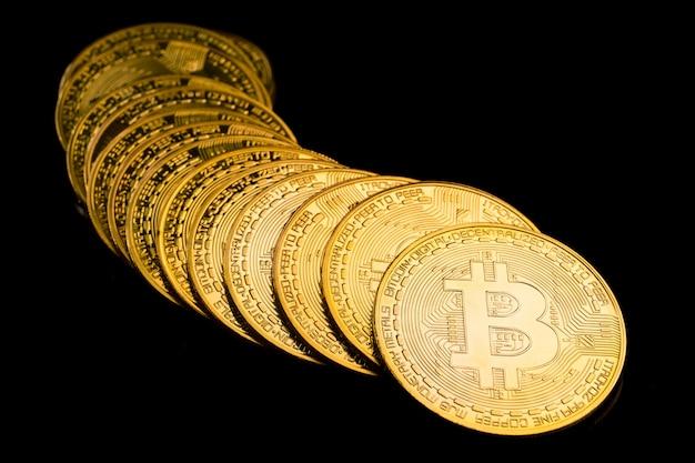 Monete d'oro con il simbolo bitcoin su sfondo nero.