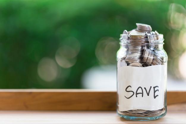 Monete del deposito di risparmio in una bottiglia di vetro trasparente