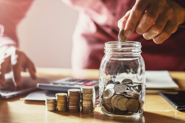 Monete della tenuta dell'uomo d'affari che mettono in vetro. concetto di risparmio di denaro e contabilità finanziaria