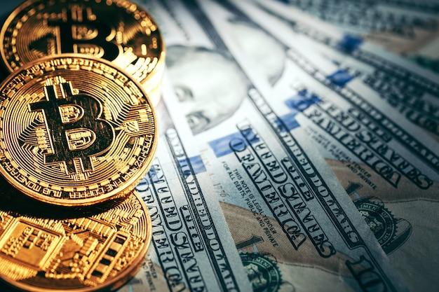 Monete dorate del bitcoin sui soldi dei dollari di carta