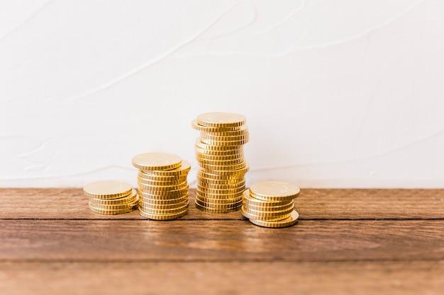 Monete dorate impilate sullo scrittorio di legno