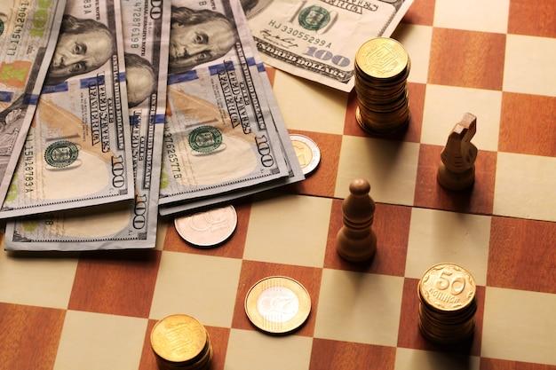 Monete e dollari della torre su una scacchiera, soldi, concetto di finanza