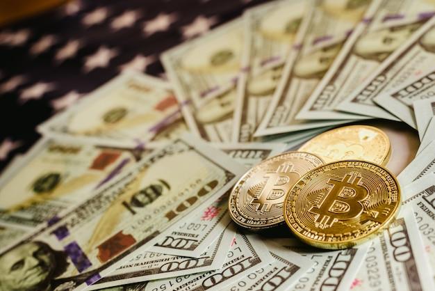 Monete fisiche di bitcoin sul fondo della bandiera americana con i dollari nei precedenti.