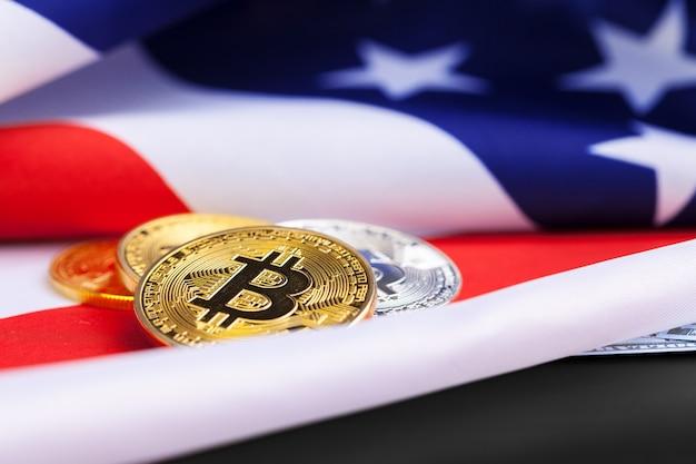 Monete fisiche di bitcoin sul fondo della bandiera americana con i dollari