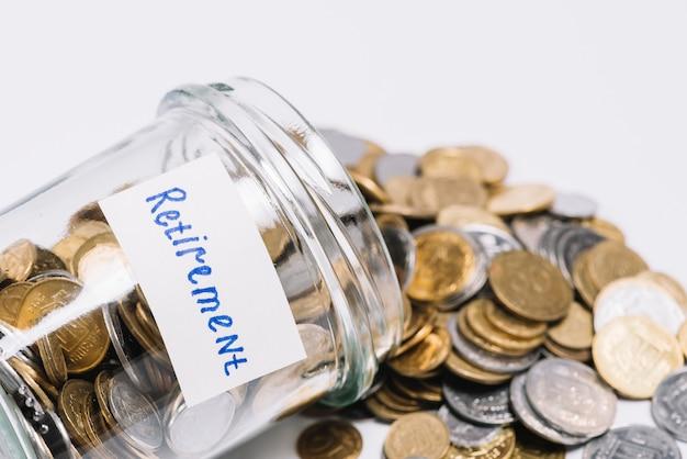 Monete fuoriuscite dal contenitore di vetro per la pensione