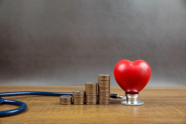 Monete impilate a forma di grafico e cuore con stetoscopio. concede un esame fisico per l'assistenza sanitaria e l'assicurazione medica.