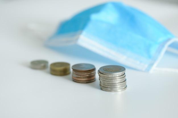 Monete impilate e maschera medica. concetto investimento, affari, finanza, coronavirus impatto crisi globale dei mercati azionari economia